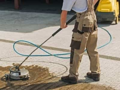 A man using a heavy duty pressure washer to clean a large brick patio.